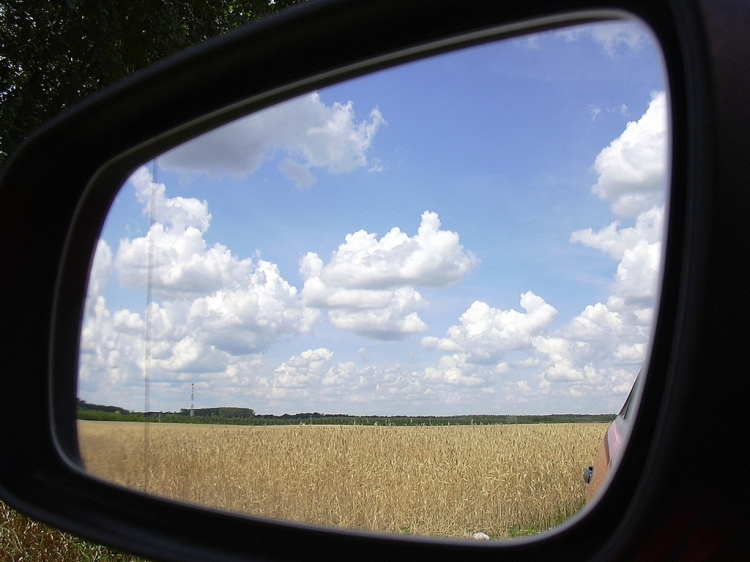Leaving the midwest represented by cornfield in rearview mirror
